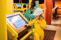 Boy operator recording operation of oil and gas process at oil and rig plant, offshore oil and gas industry, offshore. Oil and rig in the sea, operator monitor royalty free stock images