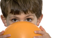 Boy with orange balloon. Cute young boy looking over top of orange balloon in front of face, white studio background Royalty Free Stock Photo