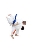 Boy with orange belt is doing throw a boy with blue belt Stock Image