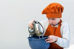 A boy in the orange dress of the chef stirs something with a mixer in a blue cup on a light background. The blond boy in the orange dress of the chef stirs stock image