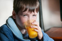 Boy with orange juice at breakfast Stock Photography