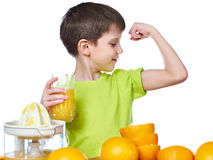 Boy with orange juice looking at biceps muscle isolated Royalty Free Stock Images