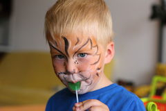 Boy with orange lion painted on his face licking lollipop Stock Images
