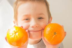Boy with oranges in his hands royalty free stock photo
