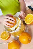 Boy with oranges makes juice in juicer isolated Royalty Free Stock Images