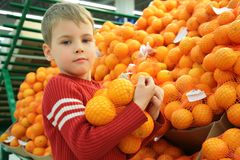Boy with oranges in shop Royalty Free Stock Photos