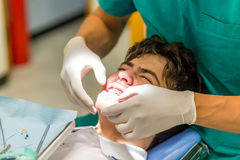 Boy and orthodontist. Guy on the dentist chair while the orthodontist is checking the brackets of edgewise dental appliance Royalty Free Stock Photos