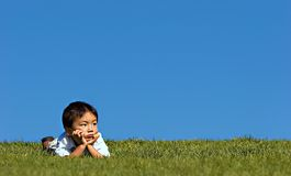 Boy Outdoors. Young asian boy in deep thought outside Royalty Free Stock Photos