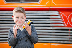 Boy outdoors with toy. Little boy with yellow Maltese bus souvenir toy in front of real bus Royalty Free Stock Images