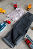 Boy outfit near car toy. Striped shirt, denim pants and blue boat shoes  yellow  red cars. Back view. Royalty Free Stock Photography