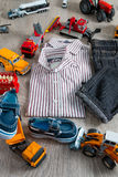 Boy outfit near car toy. Striped shirt, denim pants and blue boat shoes  yellow  red cars. Top view. Stock Photos