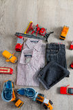 Boy outfit near car toy. Striped shirt, denim pants and blue boat shoes  yellow  red cars. Top view. Royalty Free Stock Photo