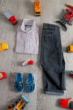 Boy outfit near car toy. Striped shirt, denim pants and blue shoes  yellow  red cars. Top view. Boy outfit near car toy. Striped shirt, denim pants and blue Stock Images