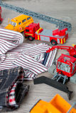 Boy outfit near set of car toy. Striped shirt, denim pants  yellow and red cars. Close up. Stock Photo