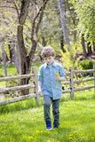 Boy outside picking flowers. Happy five year old boy standing in green grass outside picking yellow dandelions royalty free stock photos