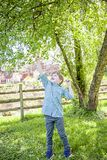 Boy outside reaching up to touch tree. Happy five year old boy standing in green grass outside picking yellow dandelions royalty free stock photography