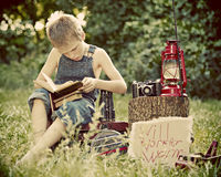 Boy outside reading. A young boy sitting outside reading a book with a camera and oil lamp on a log beside him Royalty Free Stock Photos