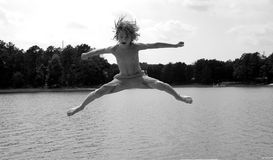 Boy over water. A boy jumping over lake in black and white stock images