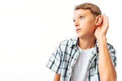 The boy overhears, put his hand to his ear to hear better, in the Studio stock photo