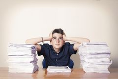 Boy overwhelmed by papers royalty free stock image