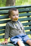Boy with pacifier on bench. Boy with pacifier sat on bench Stock Photos