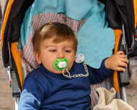 A boy with a pacifier in his baby carriage Stock Photos