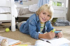 Boy (6-8) with packet of marker pens in bedroom, smiling, portrait Stock Photos