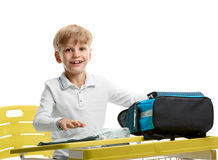 Boy packing schoolbag. Happy young boy sitting at the desk and packing schoolbag Stock Photography