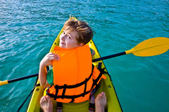 Boy paddles in a canoe at the ocean Royalty Free Stock Photos