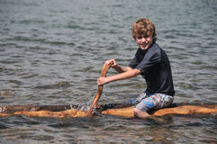 Boy paddles a raft on  lake Stock Photos