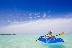 Boy paddling rubber raft Stock Image