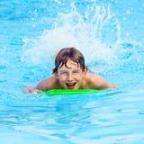 Boy paddling on the surf board. Cute boy paddling on the surf board Stock Image
