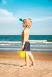 A Boy with pail and trowel on the beach looking at the horizon stock photos