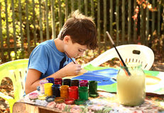 Boy paint a picture  on the autumn background Royalty Free Stock Image