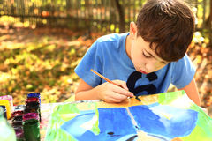Boy paint a picture  on the autumn background Royalty Free Stock Photography