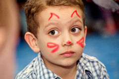 Boy with painted face. On holiday stock photography