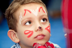 Boy with painted face. On holiday stock photos