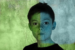 Boy with painted face. Face of a teenage boy on an old wall royalty free stock photography