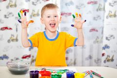 Boy with painted fingers. Jopyful boy with painted fingers, painting at home royalty free stock photo