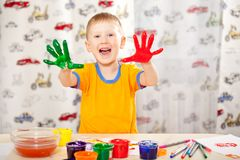 Boy with painted fingers. Funny boy with painted fingers, painting at home stock images