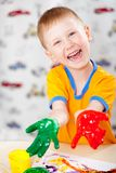 Boy with painted fingers. Funny boy with painted fingers, painting at home stock photography