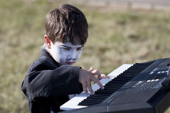 Boy. Painted boy playing keyboards outdoor Stock Photography