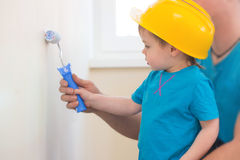 Boy painted the wall with his father Royalty Free Stock Image