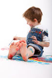 Boy painting. Funny photo of cute 5 years old boy painting on white background. Focus on feet Royalty Free Stock Photos