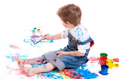 Boy painting. 5 years old boy painting with finger paints on white background royalty free stock image