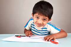 Boy painting. A boy painting with crayons on a white paper Stock Photos