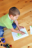 Boy painting. Boy is painting on a wooden floor Stock Photo