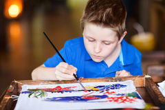Boy painting a batik Stock Photos