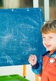 Boy painting on a blackboard. Showing his face Royalty Free Stock Photo