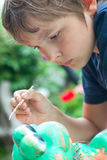 Boy painting with a brush Stock Images